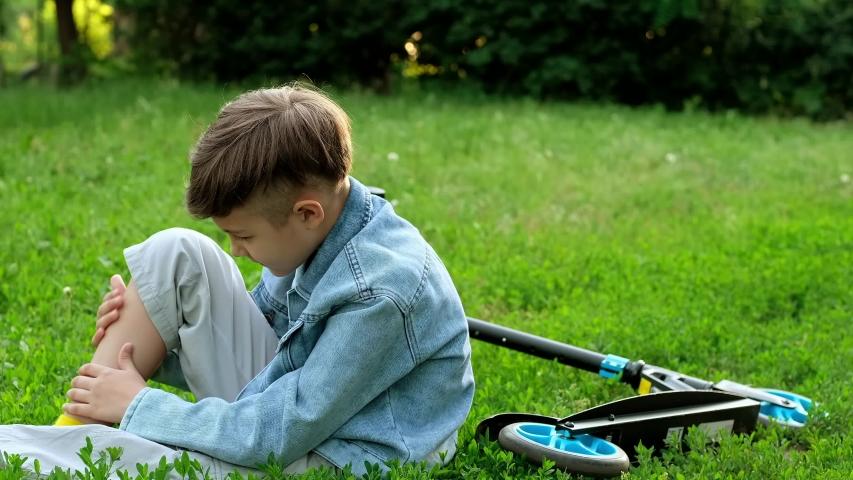 Child fell off scooter. Little boy is suffering from pain of falling off bike. | Shutterstock HD Video #1054937027