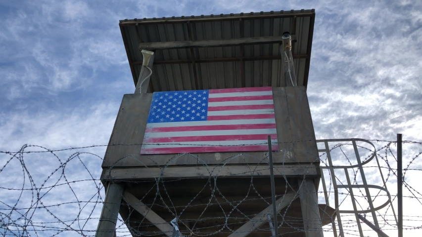 Barb-wired view protected fence on low angle and blue sky as pickup shot for protected army base area or confinement military or secured facility protection barrier. Low sun at dusk and no people. | Shutterstock HD Video #1054938242
