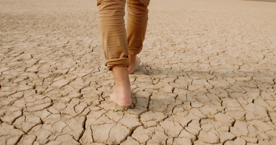 Close up shot of feet of adult man walking barefoot on bottom of dried lake or river, stepping on cracked soil ground destroyed by erosions - ecological issues concept 4k footage