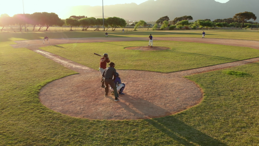 Members of a baseball team playing a game outdoors on a baseball field at sundown, the hitter hitting a pitch and making a run, seen from behind the catcher, shot with drone