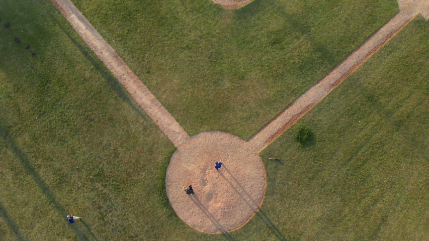 Overhead view of a baseball team playing a game outdoors on a baseball field at sundown on a sunny day, the hitter making a run and arriving back at home base as fielder catches ball, shot with drone