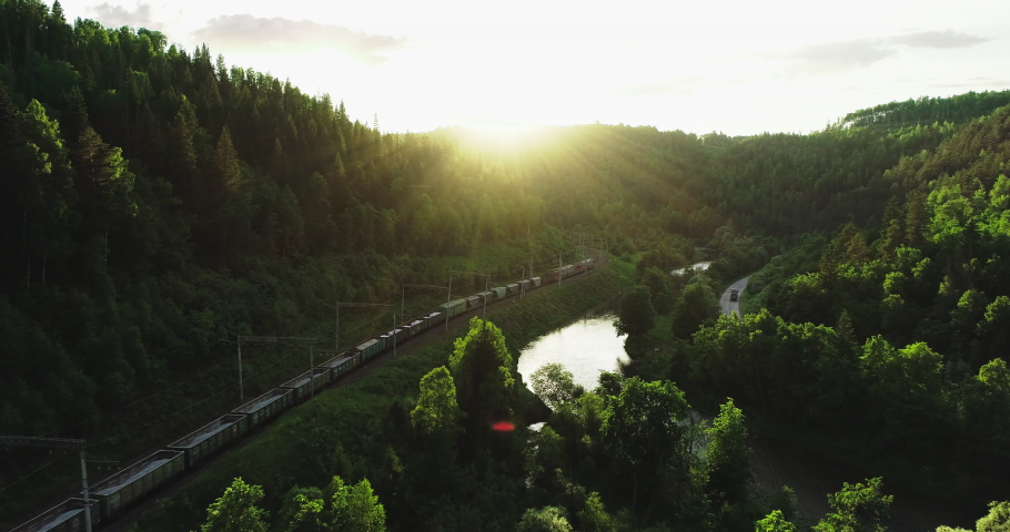 Freight train carries an electric locomotive by two-sided Trans Siberian railway near river in the forest Ural Mountains / Aerial Photography drone wide view at summer sunset