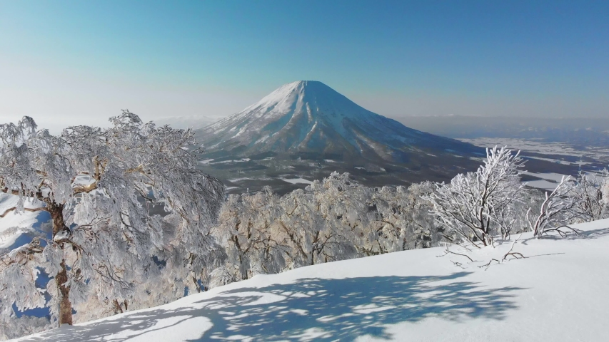 Aerial view of the snow-capped Niseko volcano in Hokkaido, Japan Royalty-Free Stock Footage #1054960940