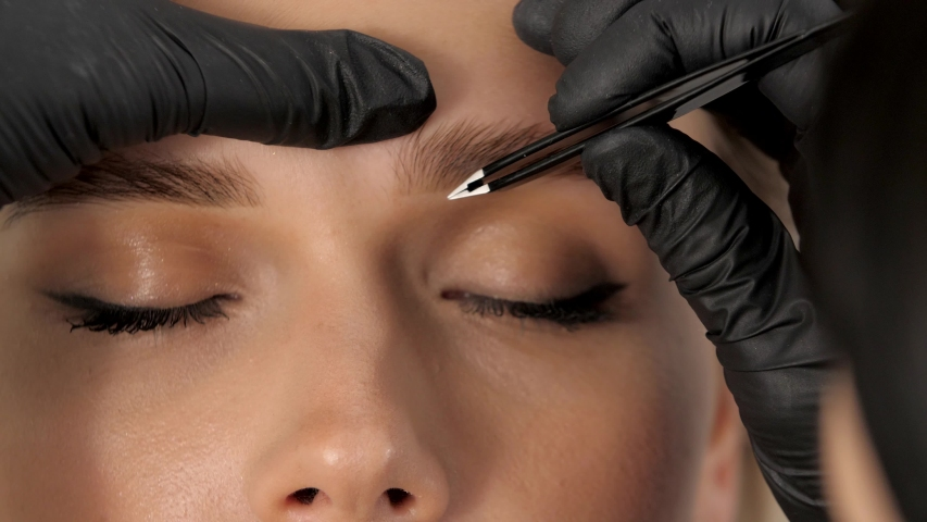 Stylist's hands in black gloves plucking eyebrows with tweezers. Beautiful attractive female face of a blonde well-groomed woman or lady. Styling and lamination of eyebrows.