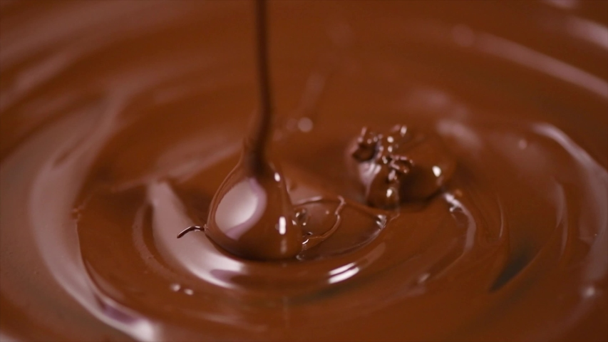 Chocolate. Pouring melted liquid premium dark chocolate. Close up of molten liquid hot chocolate swirl. Confectionery. Confectioner prepares dessert, icing. 4K UHD video, slow motion.  | Shutterstock HD Video #1054961762
