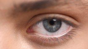 Beautiful human eye close-up. Young Woman Blue one eye macro shoot. Macro Closeup eye blinking and looking, over gray background. Eyelid, iris, Eyesight concept. 4K UHD video