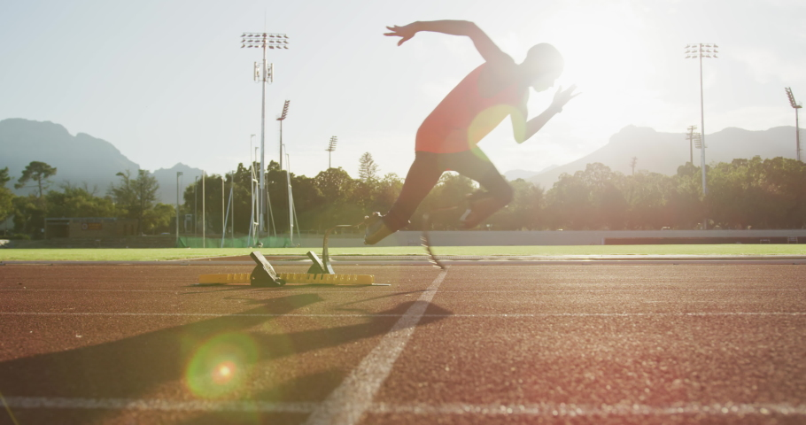Fit, disabled mixed race male athlete with prosthetic legs on a running track at an outdoor sports stadium starting a race from starting blocks, in slow motion backlit with lens flare | Shutterstock HD Video #1054962440