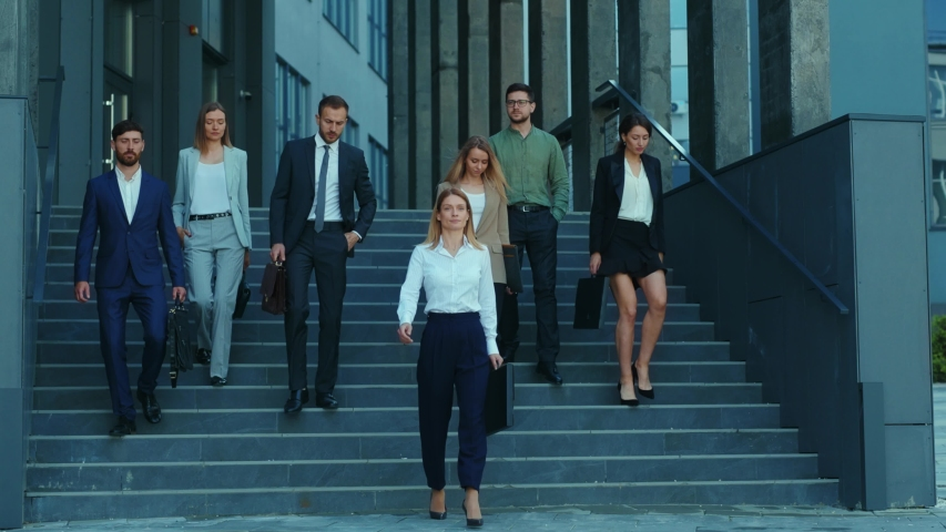 Professional company staff walking downstairs at office building. Successful and ambitious young team of co-workers and female boss. Cooperation. Career. Royalty-Free Stock Footage #1054967588