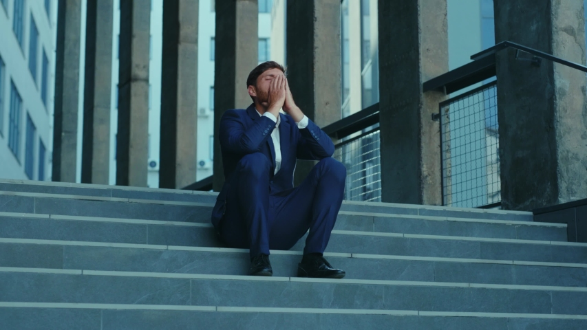 Sad furious office executive throwing his suitcase been fired lost job sitting on stairs frustrating. Unhappy fired businessman. Unemployment after lockdown. Crisis.   Shutterstock HD Video #1054967639