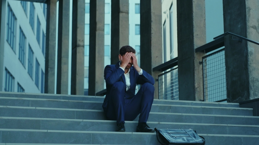 Fired corporate executive crying on stairs of office building outside. Depressed young businessman receiving dismissal note. Crisis. Unemployment.   Shutterstock HD Video #1054967642