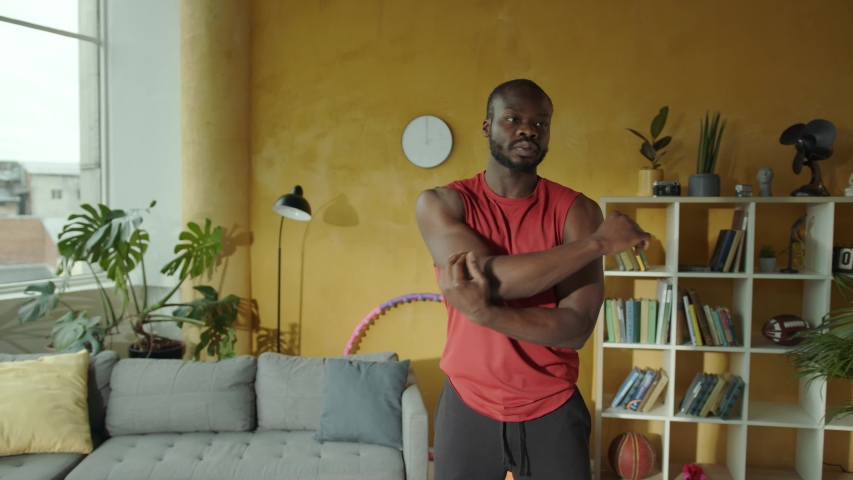 Professional black sportsman exercising aerobics doing shoulder and arm stretches warming-up before workout. Indoors. Apartment. Fitness. Sports activity.