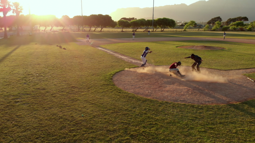 Members of a baseball team playing a game outdoors on a baseball field at sundown on a sunny day, the hitter making a run and arriving back at home base, shot with drone