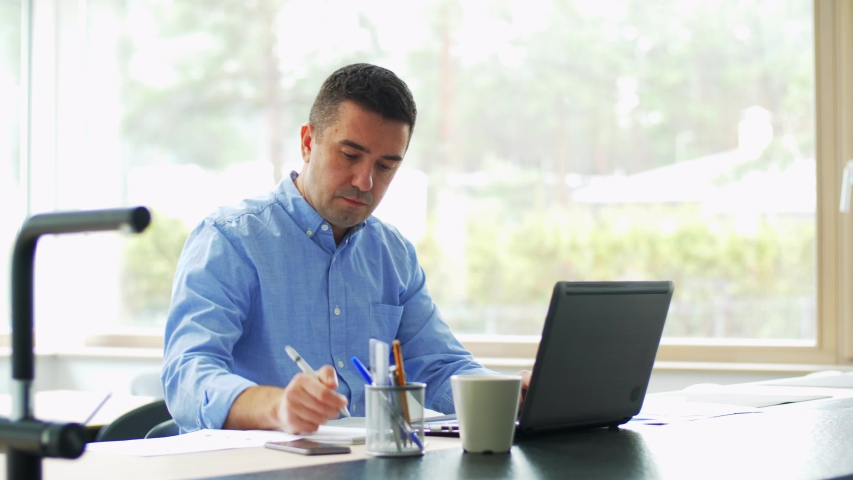 Technology, remote job and business concept - middle-aged man with laptop computer working at home office | Shutterstock HD Video #1054970204