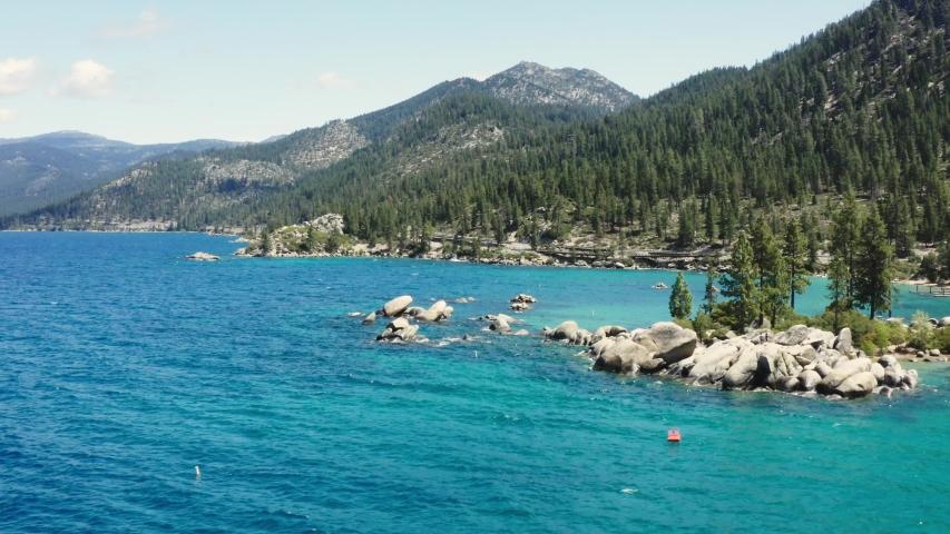 Cinematic aerial of Lake Tahoe, daytime landscape, big rocks along lake coast | Shutterstock HD Video #1054982957