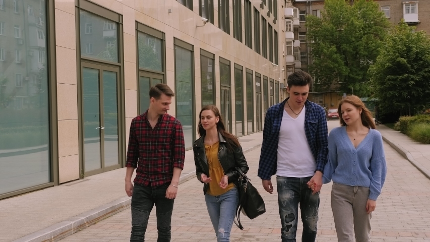 Happy friends walking together. Group of friends walking through city park together. Group of friends meeting in the city center. | Shutterstock HD Video #1054984847