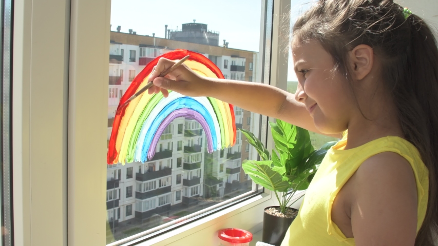 Girl painting rainbow on window during quarantine at home. Thank You Essential Workers message concept. Royalty-Free Stock Footage #1054984928