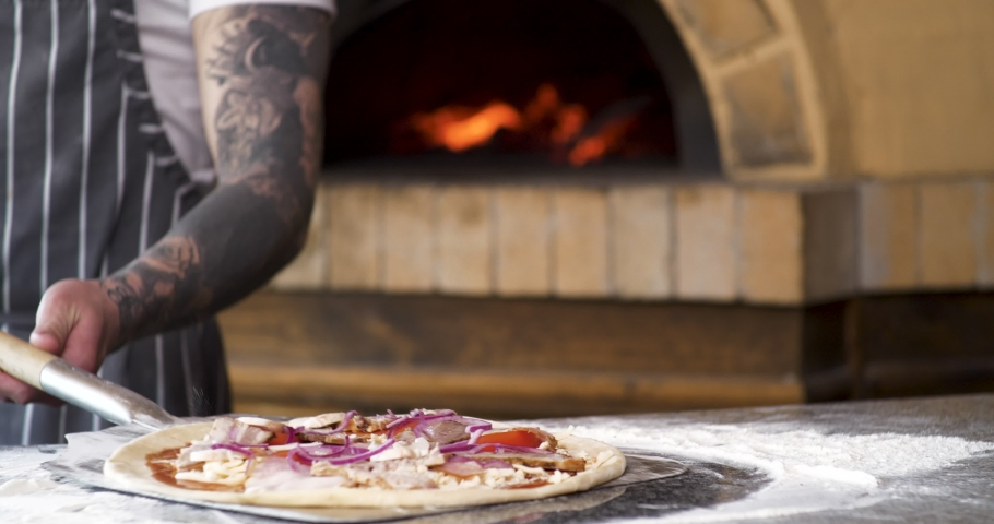 Italian Chef is Placing Pizza in Woodfired Pizza Oven using a Pizza Peel Slow motion shot. Series of Shots about Pizza. Appetizing Sauce. Slow-motion burning bonfire. Traditional Italian Food. Royalty-Free Stock Footage #1054990748