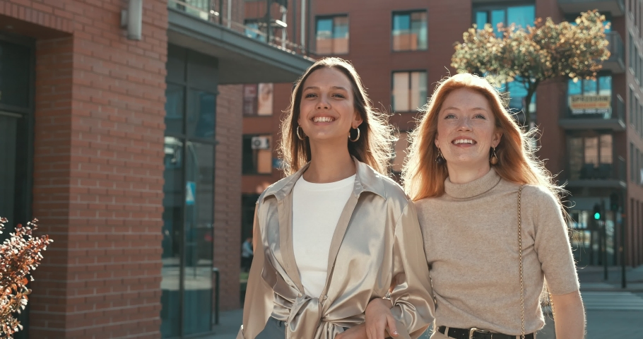 Happy and Smiling Girls Having a Walk in the City and Enjoying their youth and Free time. Having fun and Talking to each other while walking in the Town. Having stylish Outfits and charming Appearance