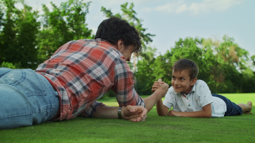 Focused father and son practising arm wrestling in meadow. Happy boy winning competition in armwrestling in park. Smiling boy celebrating success. Positive family playing together outdoors
