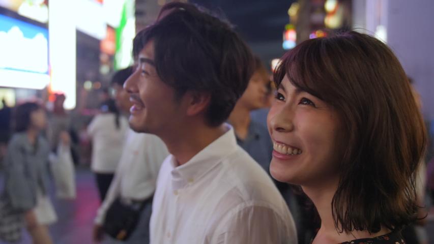 Beautiful Asian women walking through Osaka streets at night with Boyfriend tourism in Japan  Royalty-Free Stock Footage #1054994294