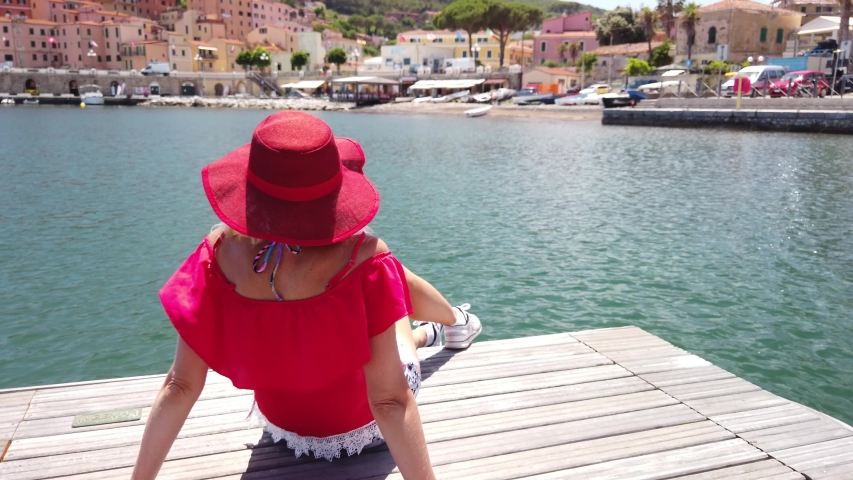 Italian woman resting and sunbathing in Rio Marina harbor of Elba island in red elegant suit. Blonde tourist girl on holiday in Italy. Rio Marina town in summer travel.