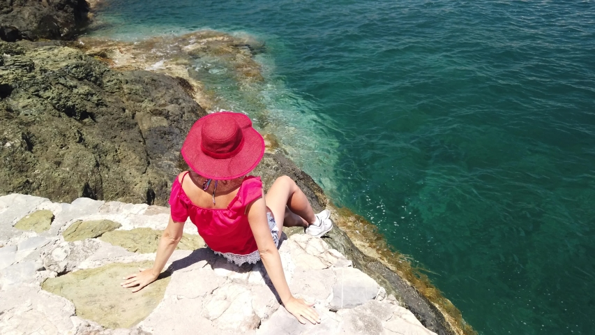 Italian woman resting in Rio Marina reef in red suit. Blonde tourist on holiday travel in Italy. Rio Marina town in summer on Elba island with clock tower of the city.