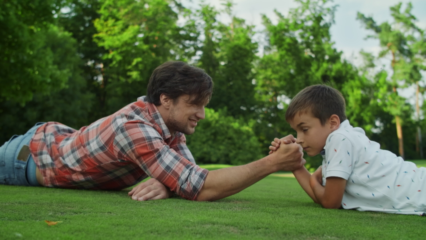 Closeup father and son lying on green grass in field. Smiling man and boy competing in arm wrestling outdoors. Positive parent and kid playing armwrestling in park. Family having fun outside