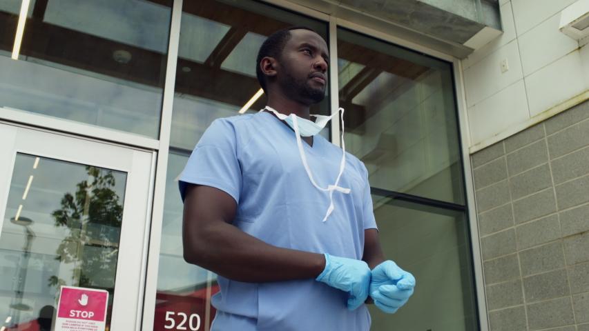 African American black male nurse doctor wearing PPE adjusting medical mask and gloves walks out of frame, low angle medium frame exterior day. 4K.
