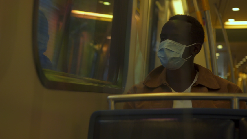 African American black man sits at window of train, wearing PPE mask while traines forward, trees and day light pass windows 4K.