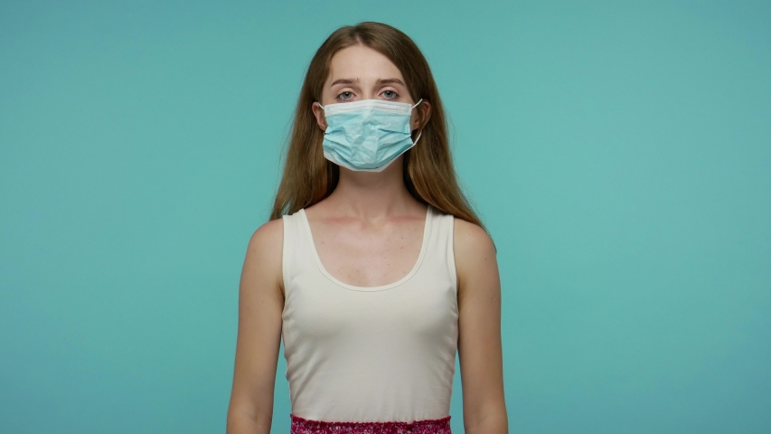Girl in summer dress putting on face hygienic medical mask to prevent respiratory infection, airborne epidemic disease as flu, contagious coronavirus. indoor studio shot isolated on blue background Royalty-Free Stock Footage #1055003084