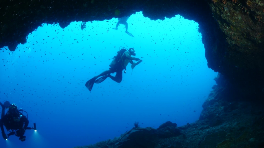 Scuba divers exploring underwater cave scenery with corals and tropical fish healthy ocean scenery