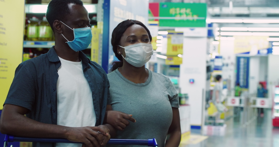 Black couple shopping in the supermarket with mask during Covid-19 Coronavirus pandemic in 2020 African people wear face mask buying food in the market