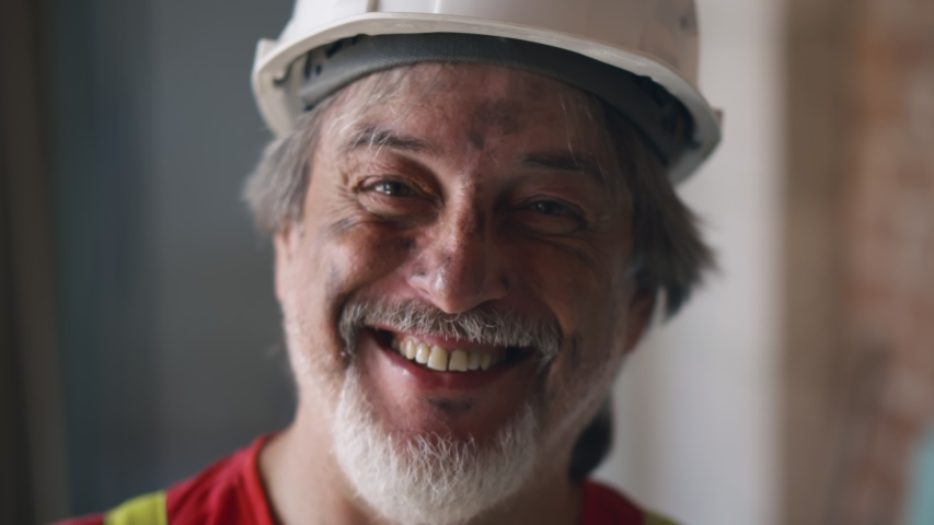 Close up portrait of cheerful mature foreman builder in safety helmet with face covered in dirt smiling at camera standing on construction site during house renovation Royalty-Free Stock Footage #1055011754