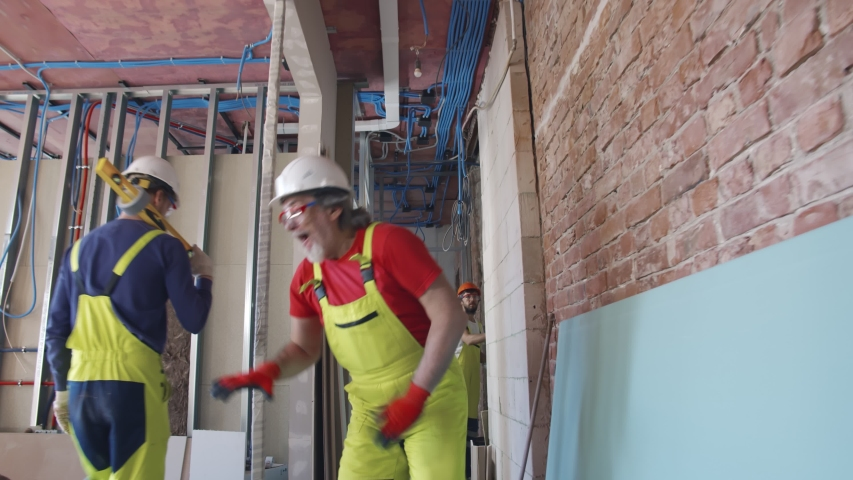 Portrait of funny middle-ages builder foreman having fun and dancing indoors on construction site relaxing during break. Happy worker dance on house renovation site Royalty-Free Stock Footage #1055011766