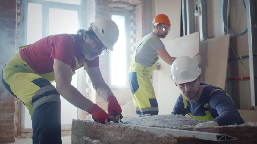 Professional workers in overalls working with rock wool insulation material cutting in. Builders in protective uniform installing thermal insulation rock wool in walls Royalty-Free Stock Footage #1055011844