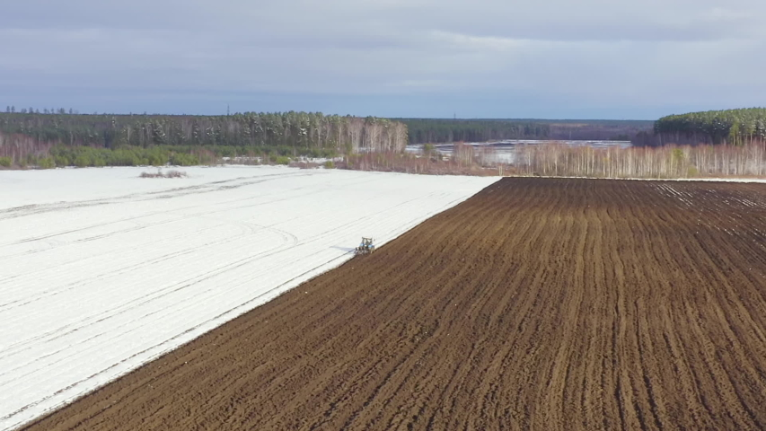 Dolly zoom. A blue tractor plows a field covered with snow. Behind the tractor is black earth. Russia, Ural, Aerial View