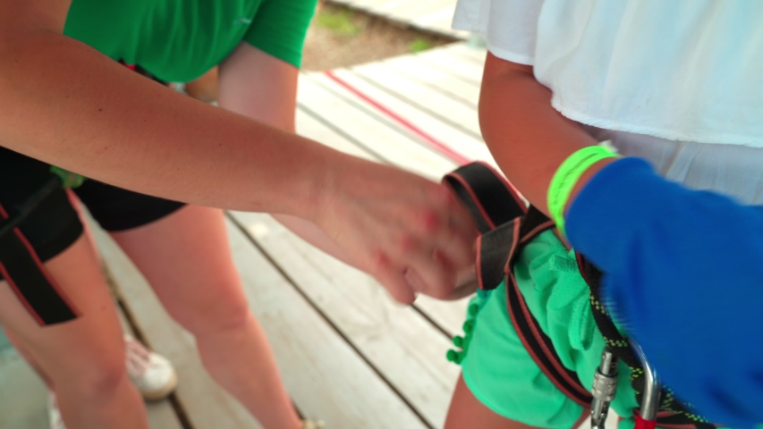 Children in the rope park. Girl instructor outfits a little girl for outdoor activities in a rope park. 4k | Shutterstock HD Video #1055020217