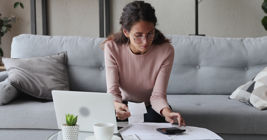 Focused serious young woman in eyewear sitting at coffee table at home, managing personal monthly budget in computer application. Concentrated lady calculating incomes outcomes utility bills. Royalty-Free Stock Footage #1055020367