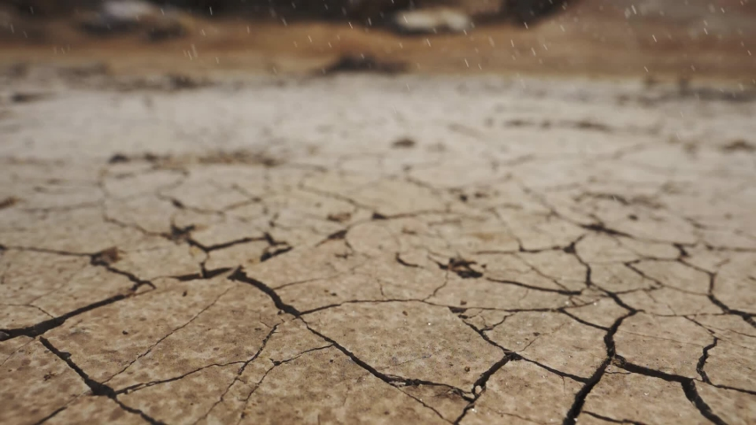 Raining in the desert. drought concept - lack of water, climate change, global warming. water drops falling. water splash, dry soil on background. ecology concept, nature landscape. water resource use