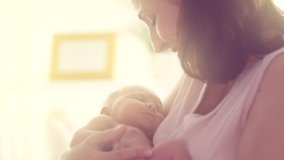 Mother and her Newborn Baby. Happy Mother holding her New born Baby girl kissing and hugging. Maternity concept. Parenthood. Motherhood. Beautiful Happy Family. Adoption. Slow motion 4K UHD video