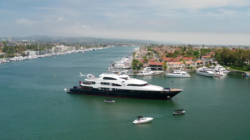 Aerial view of a wealthy billionaire luxury super yacht or mega-yacht docked in the harbor on a sunny day. | Shutterstock HD Video #1055044049