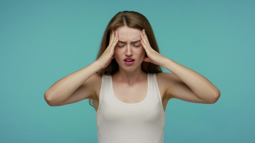 Frustrated dizzy flu-sick girl feeling unwell, suffering headache, rubbing head to relieve pain, severe migraine, stress tension, fever and flue symptoms. studio shot isolated on blue background | Shutterstock HD Video #1055044475