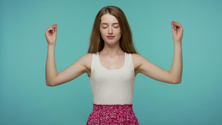 Keep calm, inner balance. Pretty girl in cute summer dress holding hands in mudra gesture with her eyes closed, meditating with concentrated thoughts, peaceful mind. studio shot, blue background | Shutterstock HD Video #1055044490