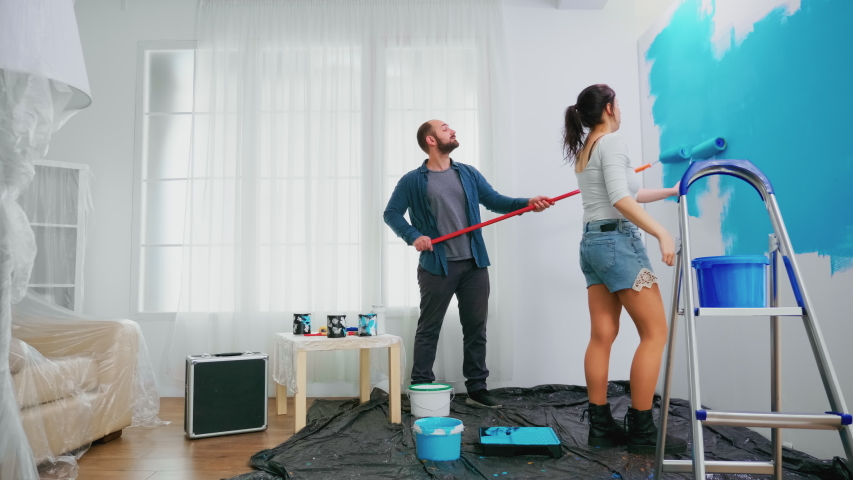 Husband and wife changing wall color using roller brush during home renovation. Home decoration and renovation in cozy apartment flat, repair and makeover   Shutterstock HD Video #1055048756