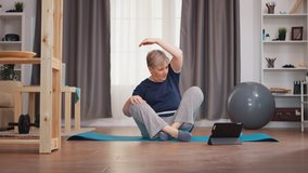 Senior woman stretching body watching online lesson sitting on yoga mat. Online learning and study, active healthy lifestyle sporty old person training workout home wellness and indoor exercising