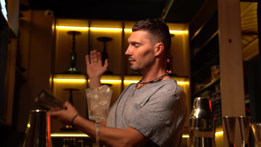 Handsome bartender tosses and juggles with a shaker for making french 75 alcohol cocktail. Barman makes drink coctail in the night club  | Shutterstock HD Video #1055064872