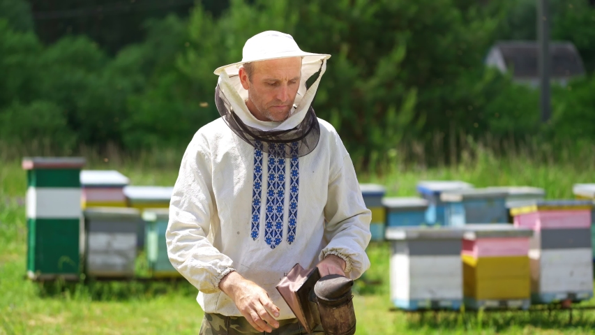 Beekeeper on apiary. Portrait of smiling man on outdoor hives background. Farmer apiarist in protective hat and in embroidery shirt looking on camera in summer day. | Shutterstock HD Video #1055066165