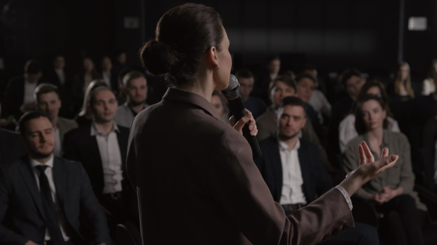 Speech of female teacher at conference meet. Confident speaker talks at scene in crowded forum hall. Woman explains motivation to people group. Teamwork study for business men at modern event indoors Royalty-Free Stock Footage #1055066531