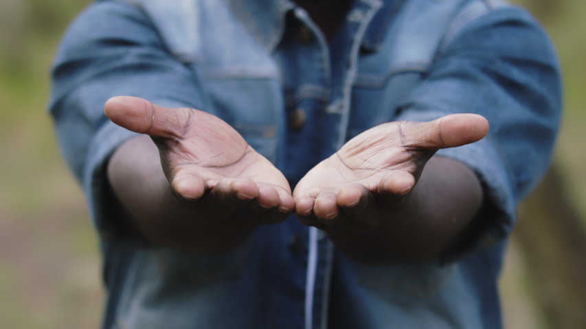 Close up. African man with outstretched hands putting the open palms together.