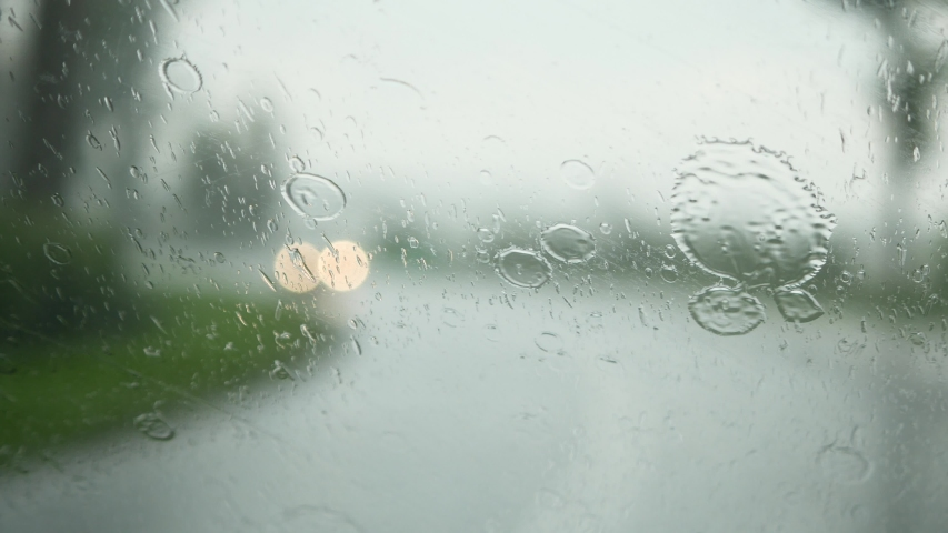 Driving in the heavy rain storm. View of a front windshield with rain drops and car wipers. | Shutterstock HD Video #1055069105